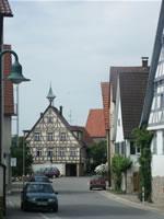 """Das Foto basiert auf dem Bild """"Schlaitdorf, Hauptstraße, Rathaus (2006)"""" aus dem zentralen Medienarchiv Wikimedia Commons. Diese Datei ist unter der Creative Commons-Lizenz Namensnennung-Weitergabe unter gleichen Bedingungen 2.5 US-amerikanisch (nicht portiert) lizenziert. Der Urheber des Bildes ist Thomas Feldes."""