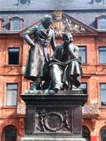 """Das Foto basiert auf dem Bild """"Denkmal der Brüder Grimm in Hanau"""" aus dem zentralen Medienarchiv Wikimedia Commons. Diese Bilddatei wurde von ihrem Urheber zur uneingeschränkten Nutzung freigegeben. Diese Datei ist damit gemeinfrei (""""public domain""""). Dies gilt weltweit. Der Urheber des Bildes ist Steschke."""
